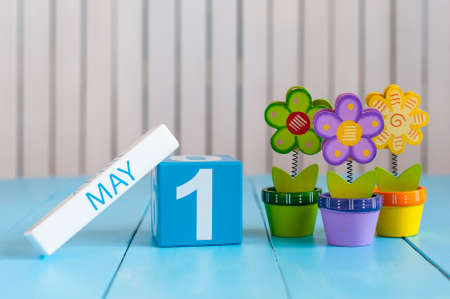 May 1st. Image of may 1 wooden color calendar on white background with flowers. Spring day, empty space for text.  International Workers Day. Stock Photo