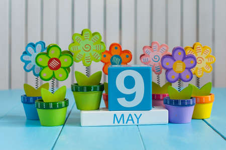 May 9th. Image of may 9 wooden color calendar on white background with flowers. Spring day, empty space for text.  Symbols Of the victory in World War II. Stock Photo