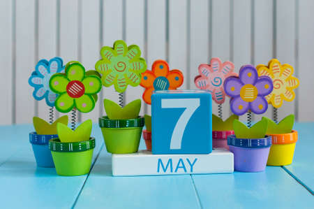 May 7th. Image of may 7 wooden color calendar on white background with flowers. Spring day, empty space for text.
