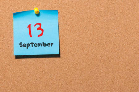 thirteen: September 13th. Day 13 of month, color sticker calendar on notice board. Autumn time. Empty space for text.
