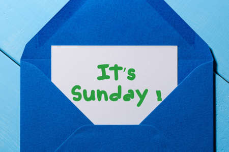 workday: The words Its Sunday written on a peace of paper in blue envelope.