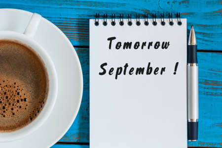 wrote: September tomorrow word wrote on white notepad on blue wood background with cup of morning coffee.