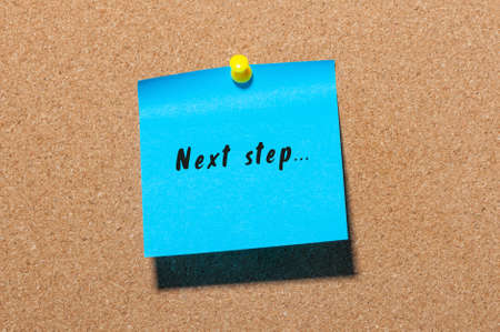 the next step: Next step words written on blue sticker pinned at notice board. Stock Photo