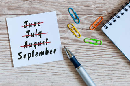 September beginning and summer end concept written at notepad on workplace background. Striked June, July, August.