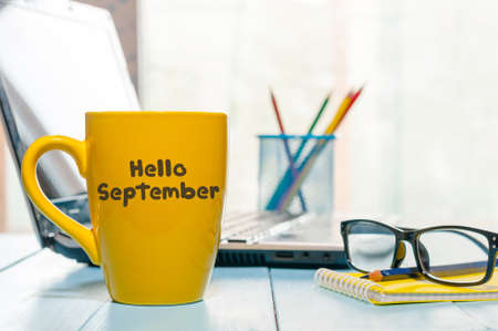 Hello September written on yellow coffee cup at teacher or student workplace. Stock Photo