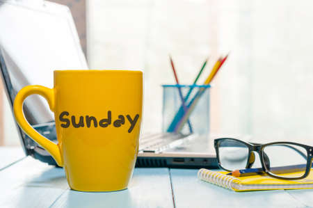 Sunday with coffee cup on table.