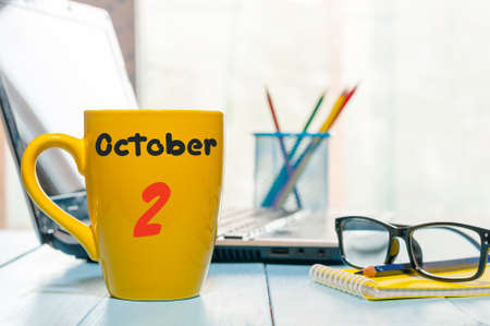 personal organiser: October 2nd. Day 2 of month, calendar on cup with hot tea or coffee at teacher workplace background. Autumn time.