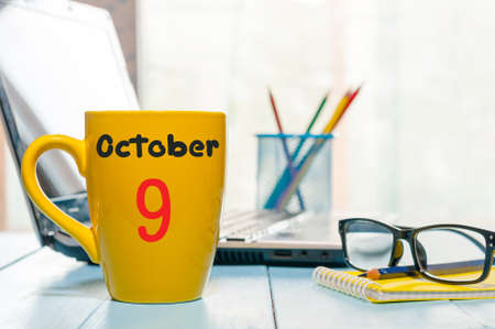 October 9th. Day 9 of month, coffee or tea yellow cup with calendar on designer workplace background. Autumn time. Empty space for text. Stock Photo