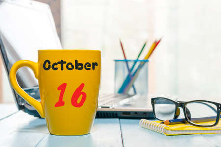 October 16th. Day 16 of month, morning tea in yellow cup with calendar on banker workplace background. Autumn time. Empty space for text. Stock Photo
