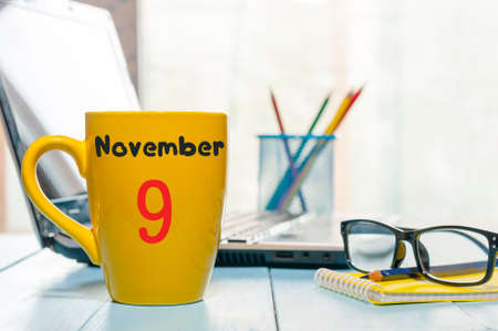 9th: November 9th. Day 9 of month, coffee or tea yellow cup with calendar on designer workplace background. Autumn time. Empty space for text.