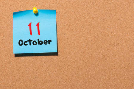 11th: October 11th. Day 11 of month, color sticker calendar on notice board. Autumn time. Empty space for text.