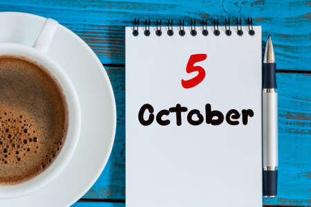 5th: October 5th. Day 5 of month, tea or coffee cup with calendar on freelancer workplace background. Autumn time. Stock Photo