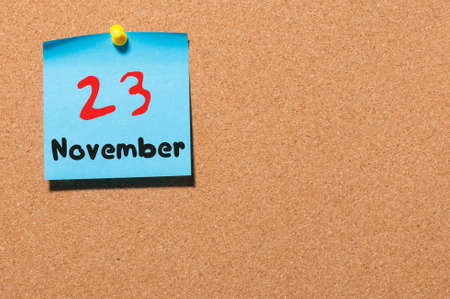 20 23 years: November 23rd. Day 23 of month, color sticker calendar on notice board. Autumn time. Empty space for text.