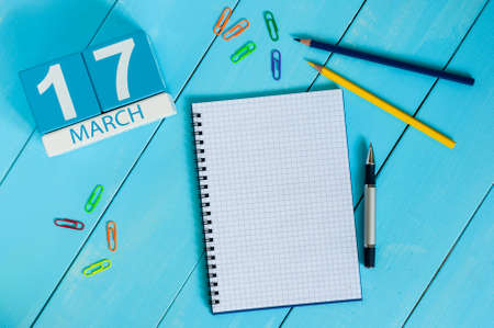 march 17th: Happy St Patricks Days save the date. March 17th. Day 17 of month, calendar on blue wooden table background with notepad. Spring time, empty space for text.