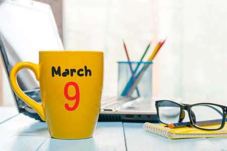 March 9th. Day 9 of month, calendar on business office background, workplace with laptop and glasses. Spring time, empty space for text.