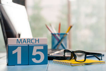 March 15th. Day 15 of month, calendar on business office background, workplace with laptop and glasses. Spring time, empty space for text. Stock Photo
