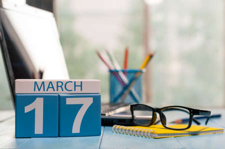 march 17th: March 17th. Day 17 of month, calendar on business office background, workplace with laptop and glasses. Spring time, empty space for text.