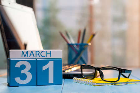 31st: March 31st. Day 31 of month, calendar on business office background, workplace with laptop and glasses. Spring time, empty space for text.