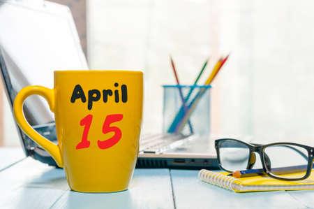 15 april. Dag 15 van de maand, kalender op zakelijke kantoor achtergrond, werkplek met laptop en een bril. Lentetijd, lege ruimte voor tekst.