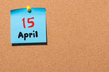 timeframe: April 15th. Day 15 of month, calendar on cork notice board, business background. Spring time, empty space for text.