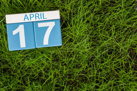 17th: April 17th. Day 17 of month, calendar on football green grass background. Spring time, empty space for text.