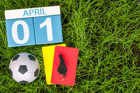 April 1st. Day 1 of month, calendar on football green grass background. Spring time, empty space for text.
