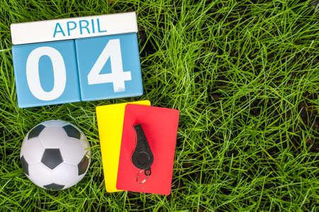 April 4th. Day 4 of month, calendar on football green grass background. Spring time, empty space for text.