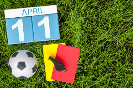 11th: April 11th. Day 11 of month, calendar on football green grass background. Spring time, empty space for text.