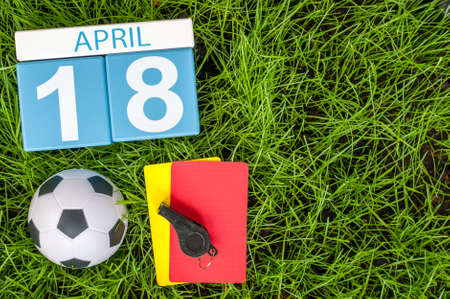personal organiser: April 18th. Day 18 of month, calendar on football green grass background. Spring time, empty space for text.