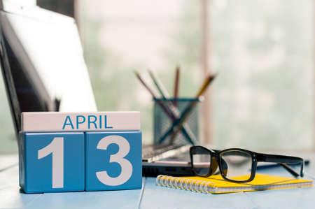 13 april. Dag 13 van de maand, kalender op zakelijke kantoor achtergrond, werkplek met laptop en glazen. Lentetijd, lege ruimte voor tekst. Stockfoto