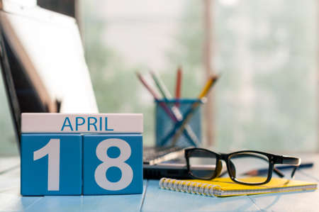 April 18st. Day 18 of month, calendar on business office background, workplace with laptop and glasses. Spring time, empty space for text.