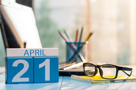 April 21st. Day 21 of month, calendar on business office background, workplace with laptop and glasses. Spring time, empty space for text. Stock Photo