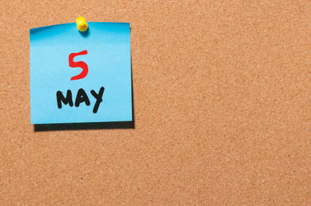 5th: May 5th. Day 5 of month, calendar on cork notice board, business background. Spring time, empty space for text.
