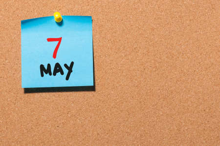 timeframe: May 7th. Day 7 of month, calendar on cork notice board, business background. Spring time, empty space for text.