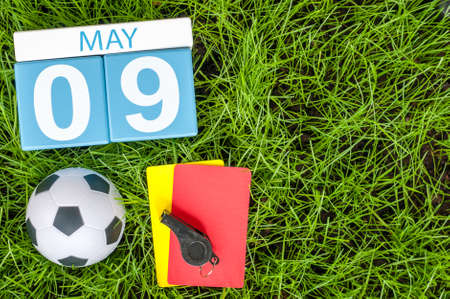 9th: May 9th. Day 9 of month, calendar on football green grass background. Spring time, empty space for text.