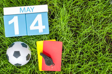 May 14th. Day 14 of month, calendar on football green grass background. Spring time.