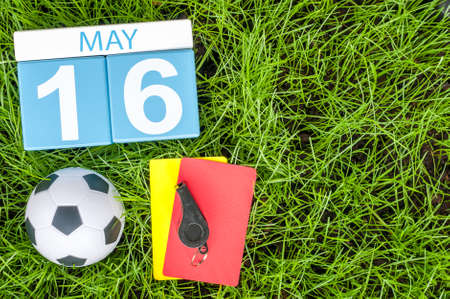 May 16th. Day 16 of month, calendar on football green grass background. Spring time, empty space for text.