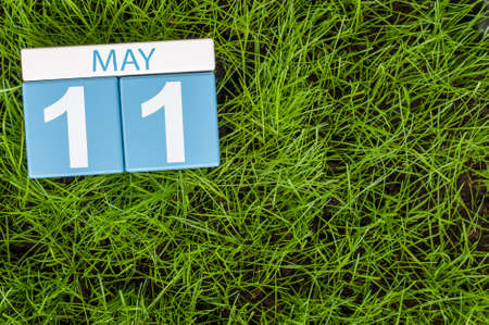 11th: May 11th. Day 11 of month, calendar on football green grass background. Spring time, empty space for text.