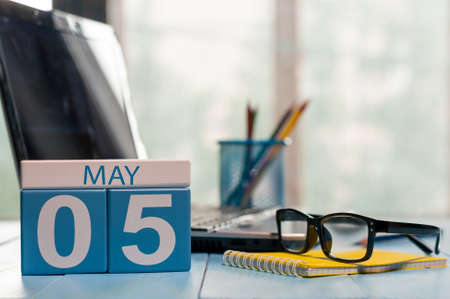 5th: May 5th. Day 5 of month, calendar on business office background, workplace with laptop and glasses. Spring time, empty space for text.