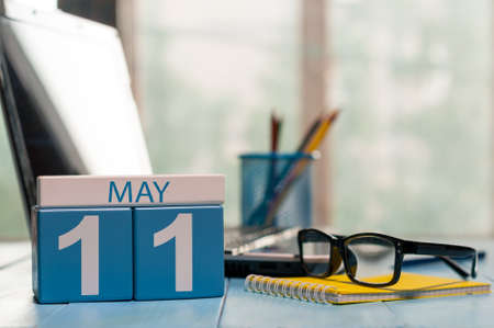11th: May 11th. Day 11 of month, calendar on business office background, workplace with laptop and glasses. Spring time, empty space for text. Stock Photo
