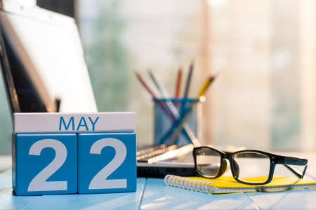 May 22nd. Day 22 of month, calendar on business office background, workplace with laptop and glasses. Spring time, empty space for text.