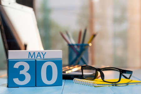 May 30th. Day 30 of month, calendar on business office background, workplace with laptop and glasses. Spring time, empty space for text.