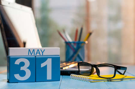 31st: May 31st. Day 31 of month, calendar on business office background, workplace with laptop and glasses. Spring time, empty space for text.