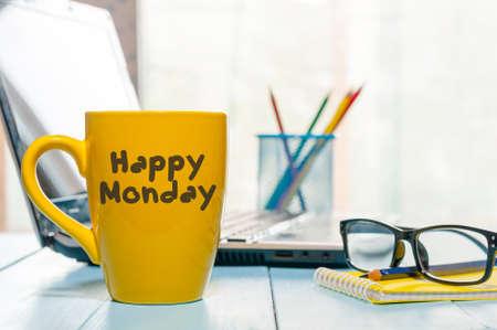 Glücklicher Montag motivierende Text auf gelbem Morgen Kaffeetasse in der Nähe von Computer im Büro am Arbeitsplatz. Business-Hintergrund. Standard-Bild