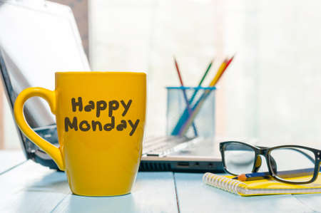 Happy Monday motivational text on yellow morning coffee cup near computer at office workplace. Business background.
