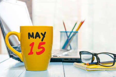 fifteen: May 15th. Day 15 of month, calendar on morning coffee cup, business office background, workplace with laptop and glasses. Spring time, empty space for text.