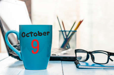 October 9th. Day 9 of month, coffee or tea blue cup with calendar on workplace background.