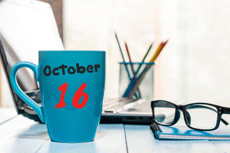 October 16th. Day 16 of month, morning tea in blue cup with calendar on banker workplace background. Autumn time. Empty space for text. Stock Photo