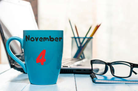 November 4th. Day 4 of month, calendar on blue cup with yea or coffee, workplace background.