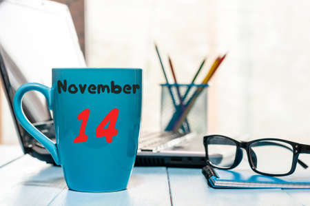 November 14th. Day 14 of month, morning coffee at blue cup with calendar on workplace background.